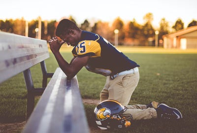 Football player kneeling and praying on field